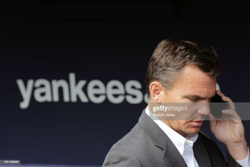 Boston Red Sox General Manager Ben Cherrington fields a phone call in the Sox dugout before the game. The Boston Red Sox play the New York Yankees at Yankee Stadium during Opening Day of the 2013 MLB season.