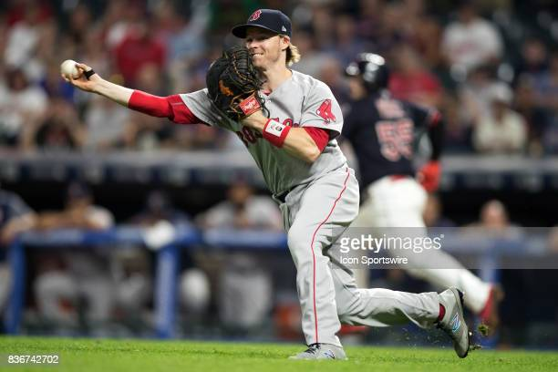 Boston Red Sox infielder Brock Holt fields a bunt by Cleveland Indians catcher Roberto Perez and throws wildly to third base allowing the winning run...