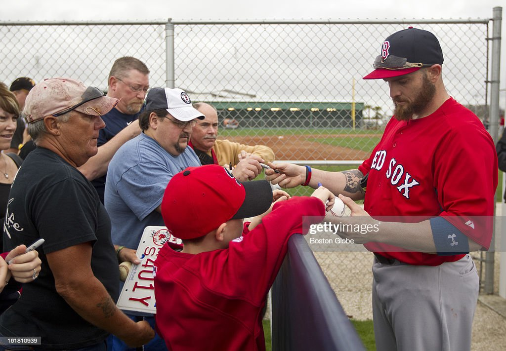 Boston Red Sox Jonny Gomes signs autographs for fans during the first full squad team workout. Day four of spring training at the Red Sox training facilities at JetBlue Park on Friday, Feb. 15, 2013.