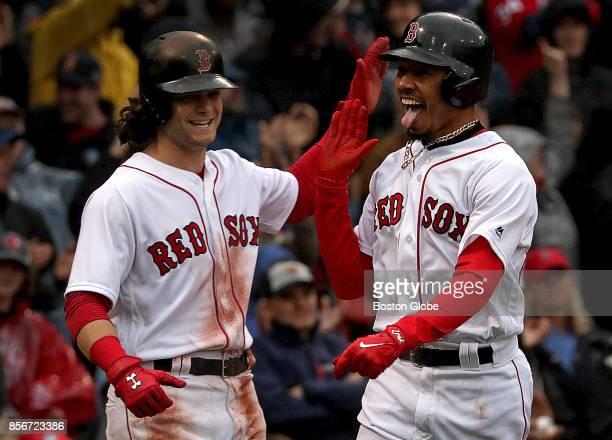 Boston Red Sox left fielder Andrew Benintendi greets Boston Red Sox right fielder Mookie Betts at home plate after both scored on a double by Boston...