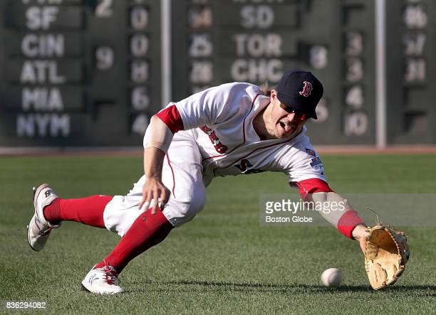 Boston Red Sox left fielder Brock Holt made a makes a diving stop of a hard hit grounder by New York Yankees left fielder Brett Gardner and the throw...