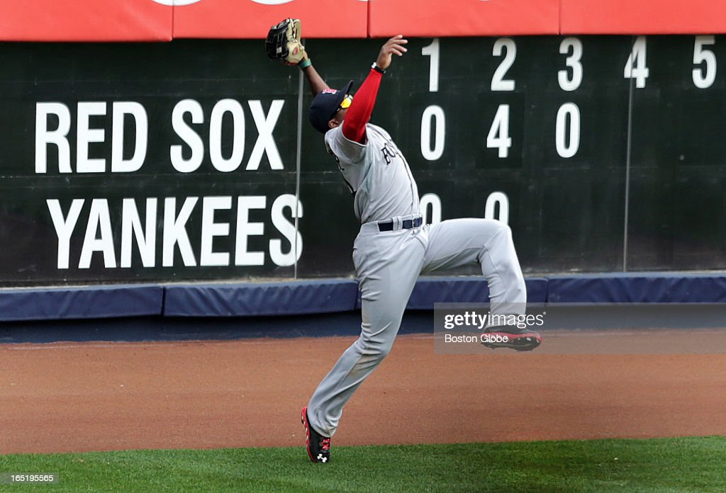 Boston Red Sox left fielder Jackie Bradley (#44) leaps and makes an acrobatic catch of a deep fly ball to left to end the third inning. The Boston Red Sox play the New York Yankees at Yankee Stadium during Opening Day of the 2013 MLB season.