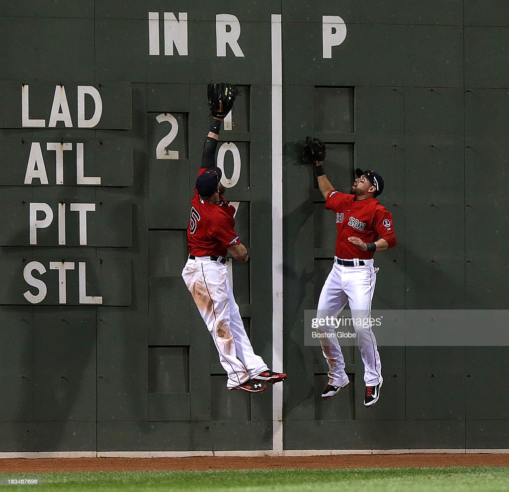 Boston Red Sox left fielder Jonny Gomes (#5) and Boston Red Sox center fielder Jacoby Ellsbury (#2) leap for a Tampa Bay Rays left fielder Kelly Johnson (#2) triple off the Green Monster in the ninth inning. The Boston Red Sox take on the Tampa Bay Rays in Game One of the ALDS at Fenway Park.