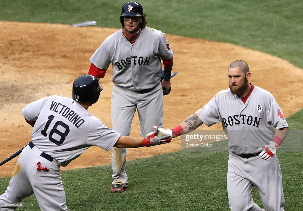 Boston Red Sox left fielder Jonny Gomes (#5) gets a hand from Boston Red Sox right fielder Shane Victorino (#18) after he and Boston Red Sox catcher Jarrod Saltalamacchia (#39) scored on an infield single by Boston Red Sox center fielder Jacoby Ellsbury (#2), not pictured, in the ninth inning. The Boston Red Sox play the New York Yankees at Yankee Stadium during Opening Day of the 2013 MLB season.