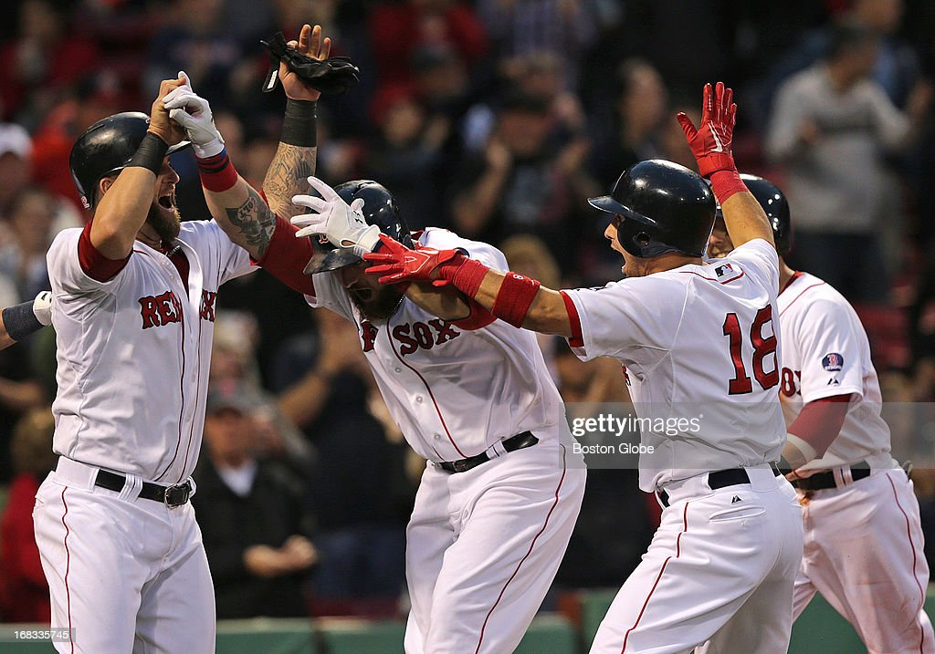Boston Red Sox left fielder Jonny Gomes (#5) is greeted at the plate after his first inning grand slam tied the game at 4-4. The Boston Red Sox take on the Minnesota Twins at Fenway Park.