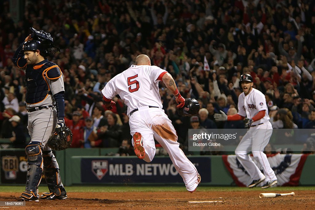 Boston Red Sox left fielder Jonny Gomes (#5) scores the game-winning run on a walk off single by Boston Red Sox catcher Jarrod Saltalamacchia (#39), not pictured, in the bottom of the ninth inning. At right is Boston Red Sox shortstop Stephen Drew (#7). The Boston Red Sox hosted on the Detroit Tigers in Game Two of the American League Championship Series at Fenway Park.