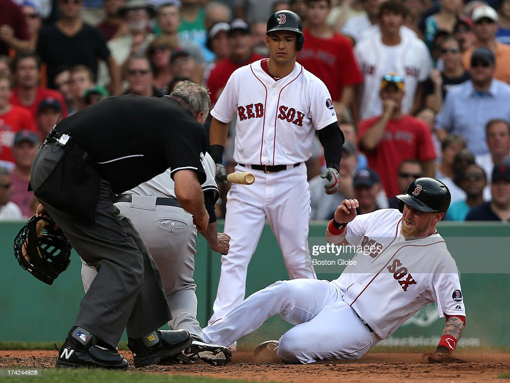Boston Red Sox left fielder Mike Carp (#37) is tagged out at home by New York Yankees starting pitcher Hiroki Kuroda (#18) as he was trying to score on a wild pitch in the fifth inning as the Boston Red Sox take on the New York Yankees in game two of a three-game series at Fenway Park.
