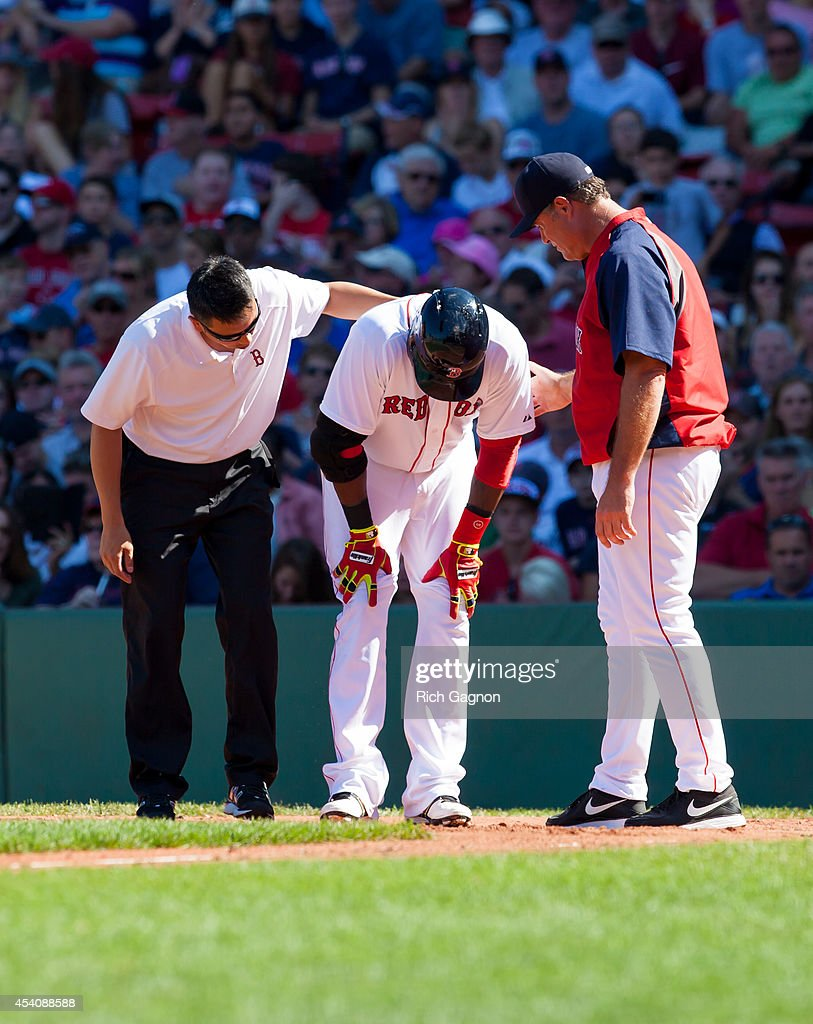 Boston Red Sox Manager John Farrell checks on David Ortiz #34 of the Boston Red Sox after he fouls a ball off his foot during the fourth inning against the Seattle Mariners at Fenway Park on August 24, 2014 in Boston, Massachusetts.