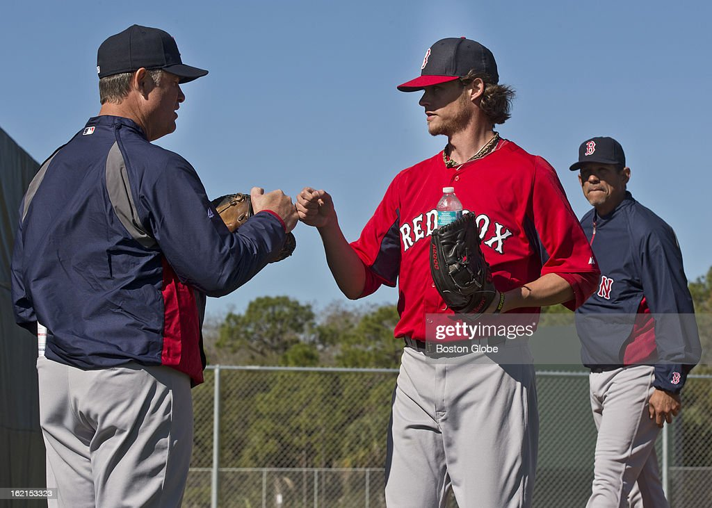 Boston Red Sox manager John Farrell fist bumps pitcher Clay Buchholz after he threw in the bull pen during spring training at JetBlue Park on Monday, Feb. 18, 2013. In the background is pitching coach Juan Nieves.