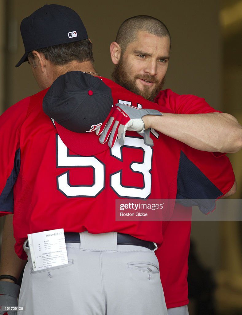 Boston Red Sox manager John Farrell hugs one of their free agent signees, Jonny Gomes in the equipment room before taking the field. Day two of spring training at the Red Sox training facilities at JetBlue Park on Wednesday, Feb. 13, 2013.