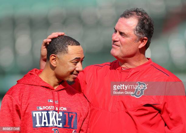 Boston Red Sox Manager John Farrell jokingly cups player Mookie Betts' head in the outfield during a practice in preparation for Game 3 of the ALCS...