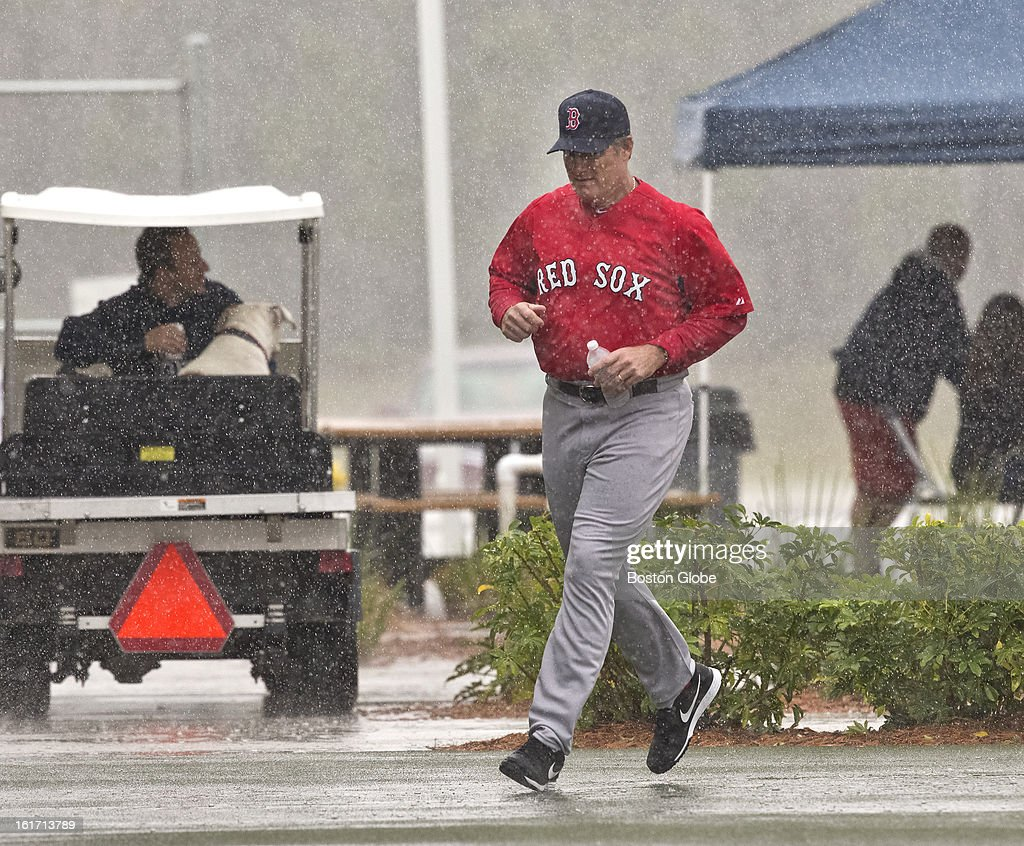 Boston Red Sox manager John Farrell runs for cover after leaving the covered batting cage back to their clubhouse. Day three of spring training at the Red Sox training facilities at JetBlue Park on Thursday, Feb. 14, 2013.