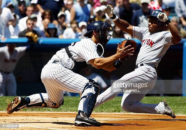 Boston Red Sox outfielder Rickey Henderson scores on a sacrifice fly in the top of the first inning as New York Yankees catcher Jorge Posada catches...