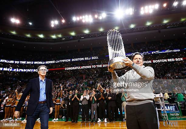 Boston Red Sox owner and CEO John Henry and chairman Tom Warner hold up the World Series trophy prior to the home opener between the Boston Celtics...