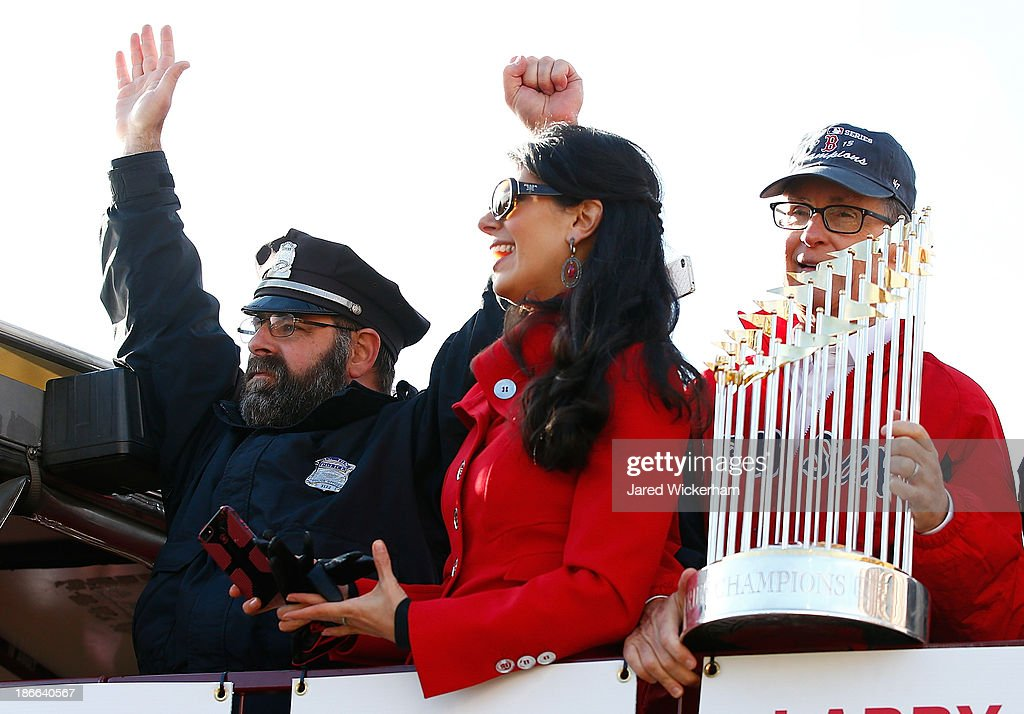 Boston Red Sox owner John Henry holds up the World Series trophy next to Boston Police officer Steve Horgan during the World Series victory parade on November 2, 2013 in Boston, Massachusetts.