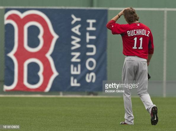 Boston Red Sox pitcher Clay Buchholz walks off the practice field after throwing with a trainer in the outfield during first full squad team workout...