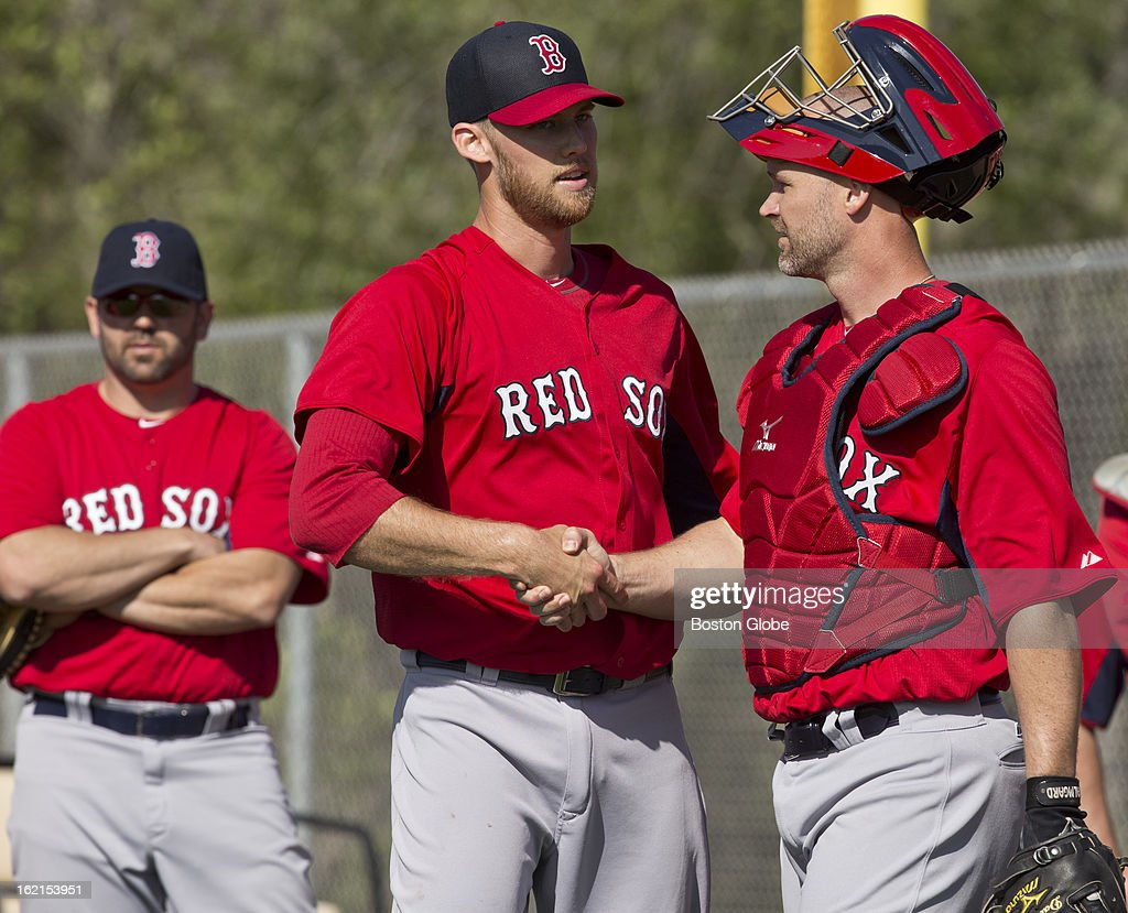 Boston Red Sox pitcher Daniel Bard, middle, shakes hands with catcher David Ross after a throwing session in the bull pen as Jason Varitek, special assistant to the general manager, looks on during spring training at JetBlue Park on Tuesday, Feb. 19, 2013.