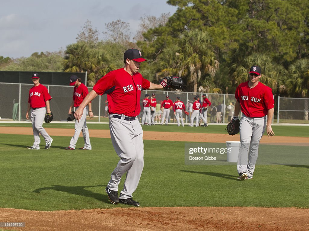 Boston Red Sox pitcher John Lackey takes a throw from Lyle Overbay as he covers first base during the first official spring training day for the Boston Red Sox pitchers and catchers at JetBlue Park on Tuesday, Feb. 12, 2013.