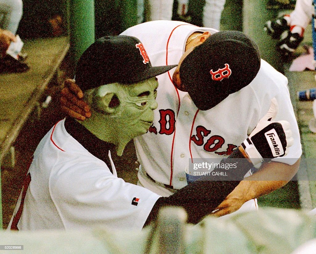 Boston Red Sox pitcher Pedro Martinez (R), wearing a 'Yoda' mask, gives a thumbs up to fellow teammates during their game against the Oakland Athletics, 27 August in Boston, MA. The Athletics won the game 6-3.
