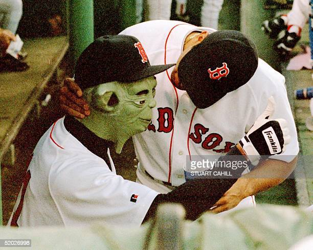 Boston Red Sox pitcher Pedro Martinez wearing a 'Yoda' mask gives a thumbs up to fellow teammates during their game against the Oakland Athletics 27...