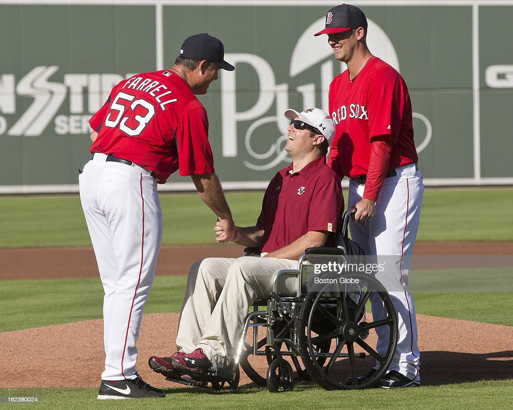 Boston Red Sox pitcher Terry Doyle helps his former Boston College teammate Peter Frates, who has been battling ALS for the past 18 months, as he presents the game ball to manager John Farrell before Boston College play the Red Sox at JetBlue Park on Thursday, Feb. 21, 2013.