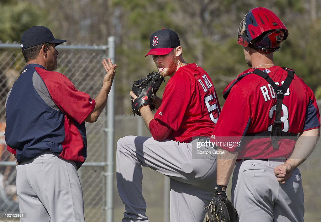 Boston Red Sox pitching coach Juan Nieves, left, talks to pitcher Daniel Bard, middle, and catcher David Ross, right, after Bard threw in the bull pen during spring training at JetBlue Park on Tuesday, Feb. 19, 2013.