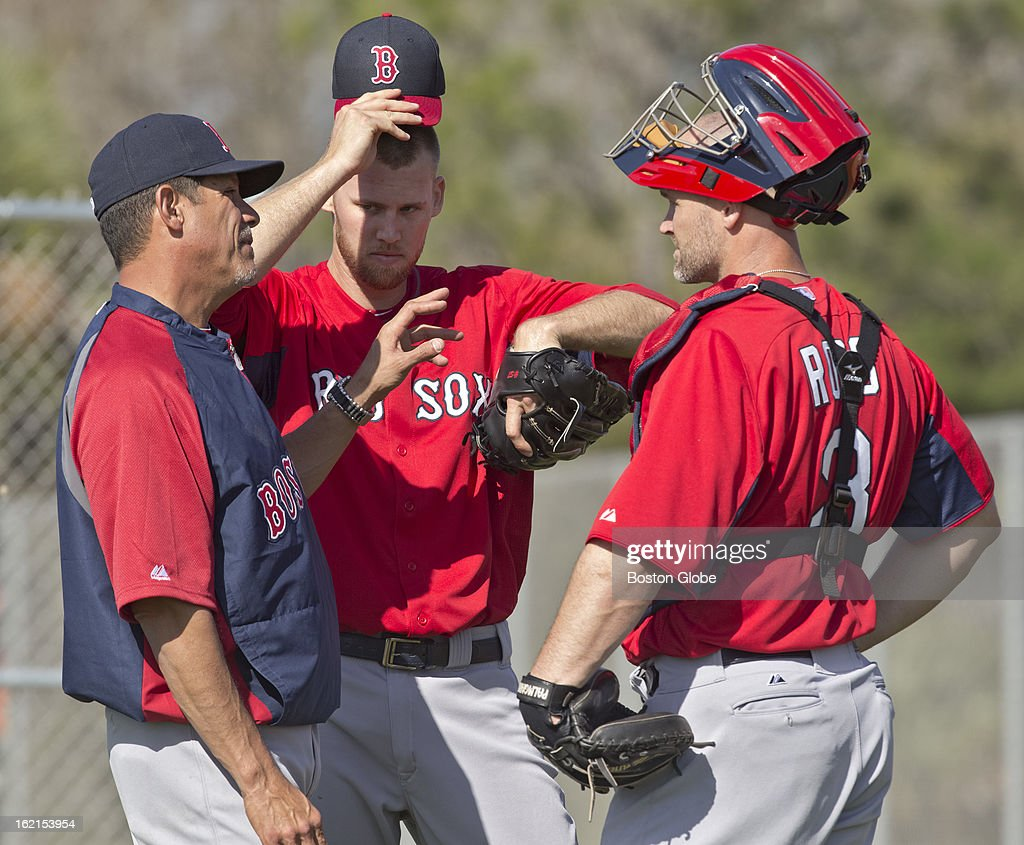 Boston Red Sox pitching coach Juan Nieves talking to pitcher Daniel Bard, middle, and catcher David Ross, right, after Bard threw in the bull pen during spring training at JetBlue Park on Tuesday, Feb. 19, 2013.