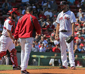 Boston Red Sox pitching coach Juan Nieves visits Boston Red Sox starting pitcher Brandon Workman on the mound during the six run third inning The...