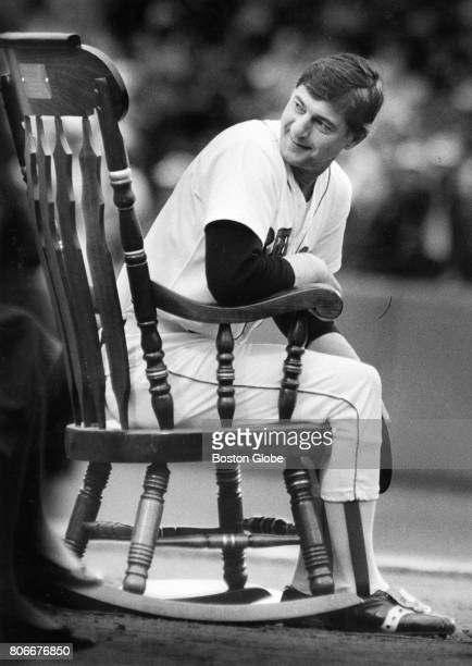 Boston Red Sox player Carl Yastrzemski looks back at his family from a rocking chair presented by media members during a ceremony before his last...