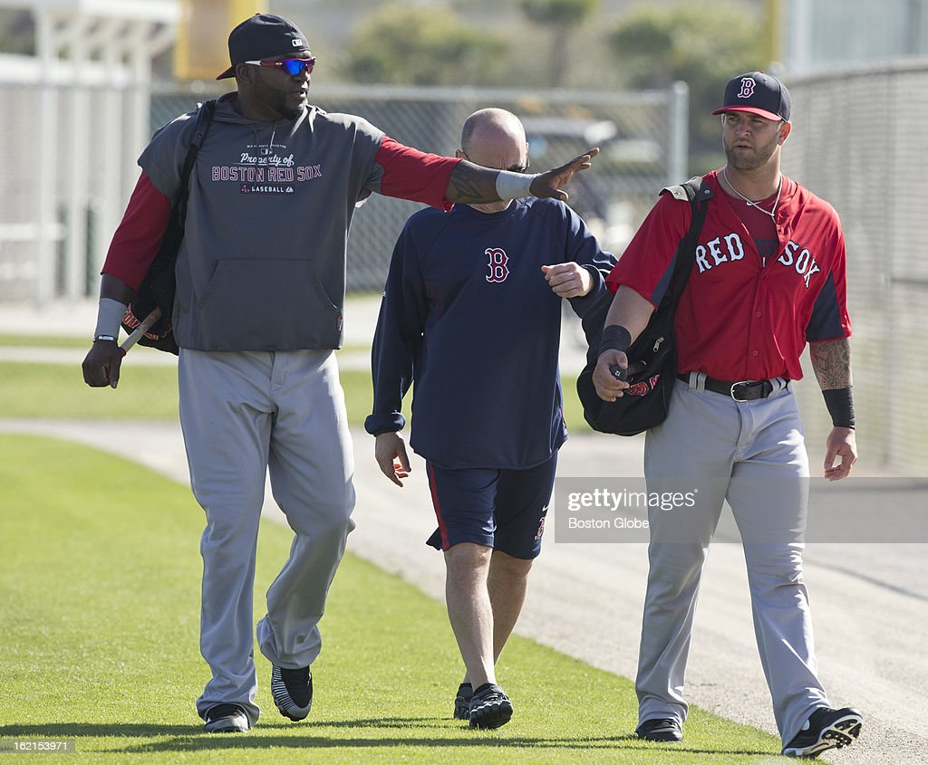 Boston Red Sox player David Ortiz, left, and Mike Napoli, right, walk off the field with strength and conditioning coach Mike Boyle after performing agility work during spring training at JetBlue Park on Tuesday, Feb. 19, 2013.
