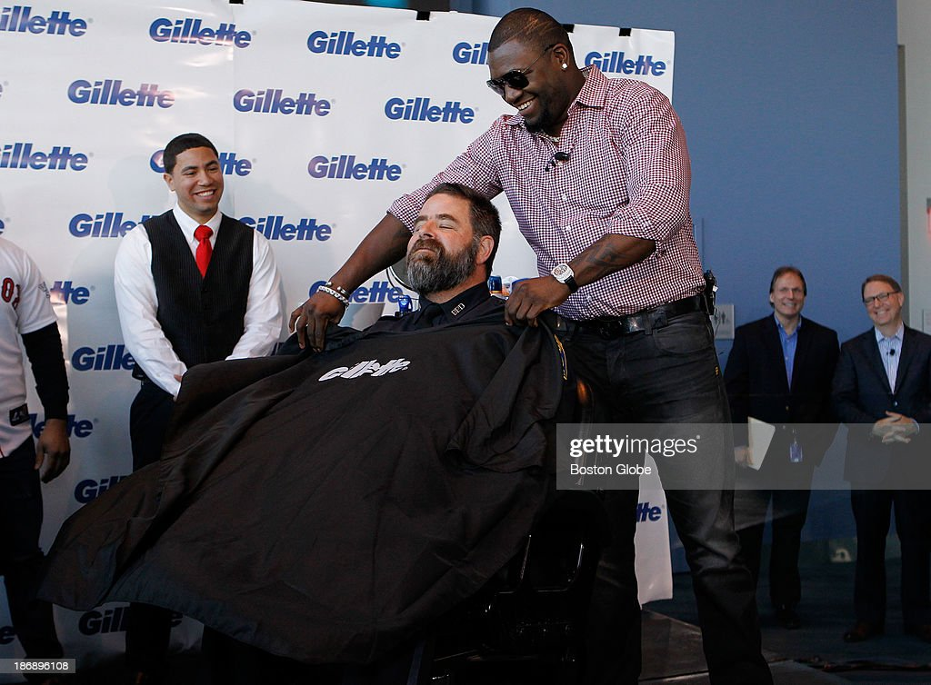 Boston Red Sox player David Ortiz puts an apron over Bullpen officer Steve Horgan before Horgan shaves his beard off at Gillette World Shaving Headquarters in Boston on November 4, 2013. Gillette donated $100,000 to the One Fund Boston after the shave.