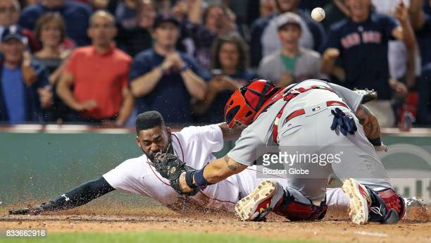Boston Red Sox player Jackie Bradley Jr dives headfirst and beats the tag of Cardinals catcher Yadier Molina who can't hold on to the ball as he...