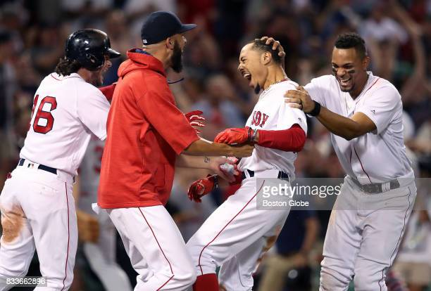 Boston Red Sox player Mookie Betts second from right is mobbed by teammates after his gamewinning walkoff double in the bottom of the ninth inning...