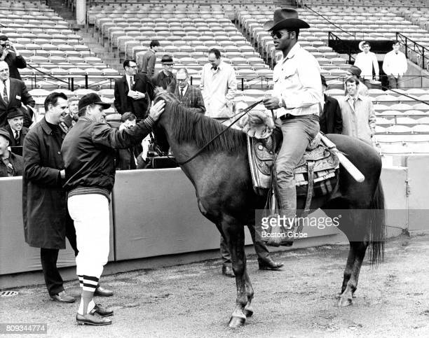 Boston Red Sox player Reggie Smith rides into Fenway Park in Boston on Windy as manager Dick Williams pets the horse on Apr 23 1969