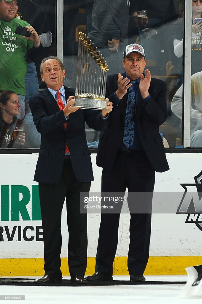 Boston Red Sox President and CEO Larry Lucchino, and President Cam Neely of the Boston Bruins show the crowd the Major League Baseball World Series trophy during a timeout against the Anaheim Ducks at the TD Garden on October 31, 2013 in Boston, Massachusetts.