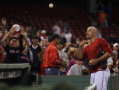 Boston Red Sox relief pitcher Alfredo Aceves tosses balls to fans at the end of the game as the Boston Red Sox take on the Tampa Bay Rays at Fenway...