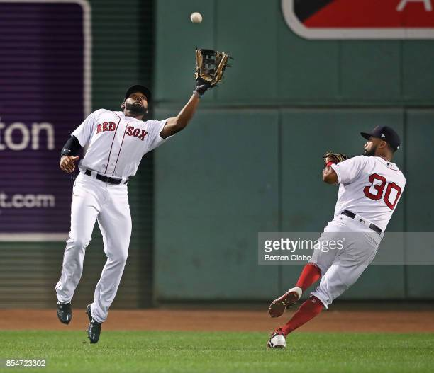 Boston Red Sox right fielder Chris Young right peels away at the last second to avoid a collision with center fielder Jackie Bradley Jr left who...