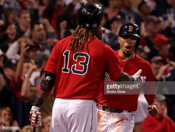 Boston Red Sox right fielder Mookie Betts is greeted at home plate by Boston Red Sox designated hitter Hanley Ramirez after Betts scored the game...