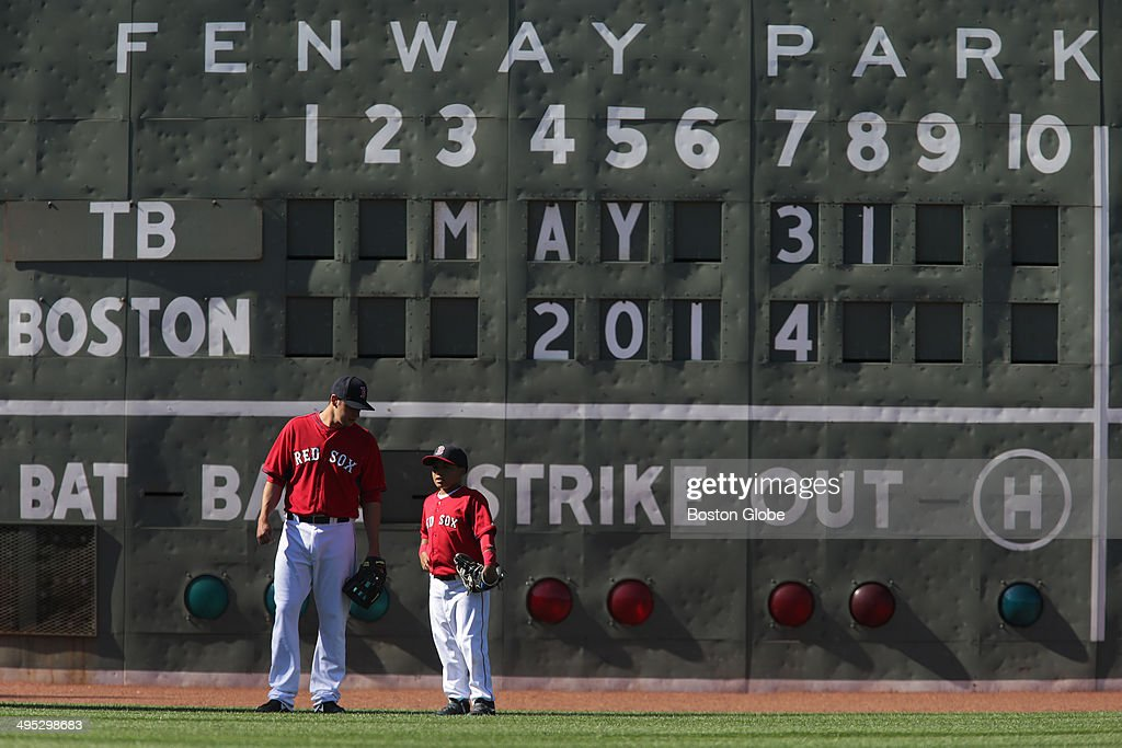 Boston Red Sox rookie right fielder Alex Hassan (#68) talks with DAngelo Ortiz, David Ortiz's son in the outfield as the Red Sox took batting practice. The Boston Red Sox host the Tampa Bay Rays in Game two of a three game series at Fenway Park.