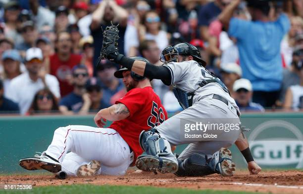 Boston Red Sox Sam Travis is tagged out at home by New York Yankees catcher Austin Romine during the second inning of the first game of a double...