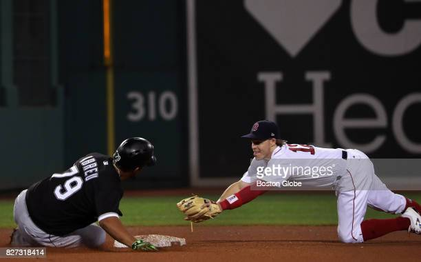 Boston Red Sox second baseman Brock Holt and Chicago White Sox first baseman Jose Abreu race to the plate as Abreu tries to stretch a hit into a...