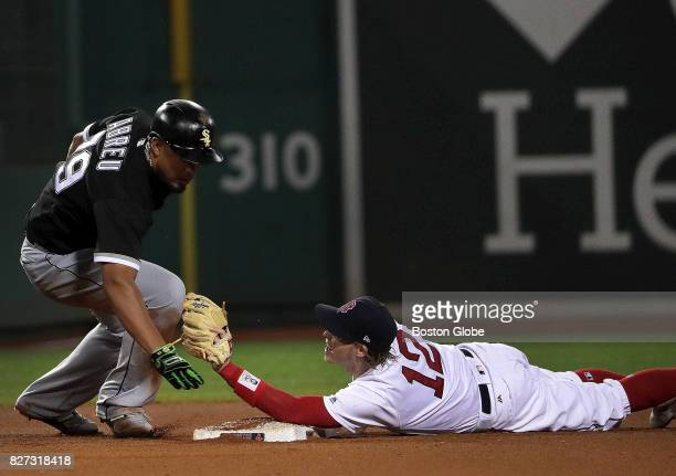 Boston Red Sox second baseman Brock Holt applies the tag to Chicago White Sox first baseman Jose Abreu who tried to stretch a hit into a double in...