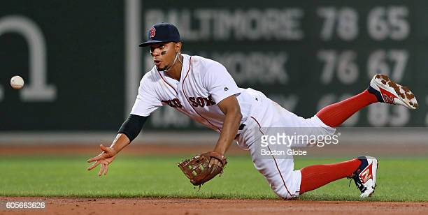Boston Red Sox short stop Xander Bogaerts throws the ball from his knees after sliding to stop the ball for a double play during the top of the third...