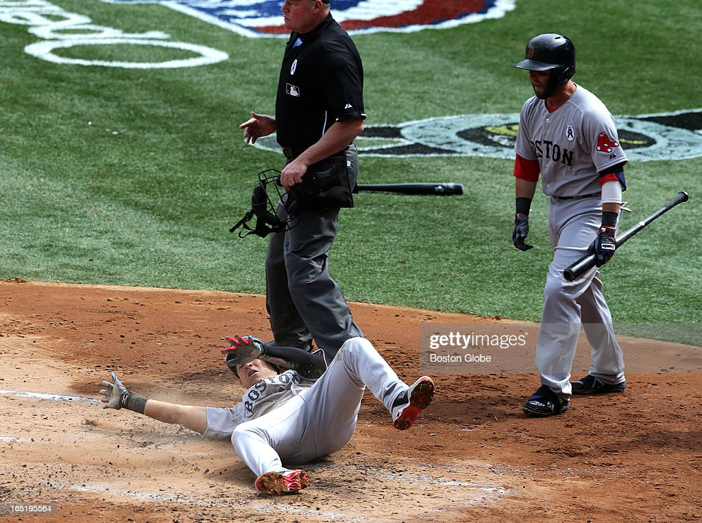 Boston Red Sox shortstop Jose Iglesias (#10) slides and rolls as he scores during a four run second inning. The Boston Red Sox play the New York Yankees at Yankee Stadium during Opening Day of the 2013 MLB season.