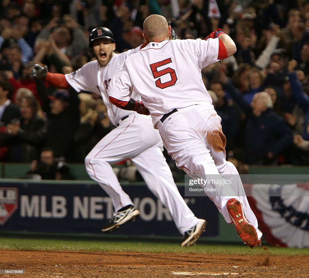 Boston Red Sox shortstop Stephen Drew (#7) and Boston Red Sox left fielder Jonny Gomes (#5) celebrate as Gomes crosses home plate with the winning run. The Boston Red Sox hosted on the Detroit Tigers in Game Two of the American League Championship Series at Fenway Park.