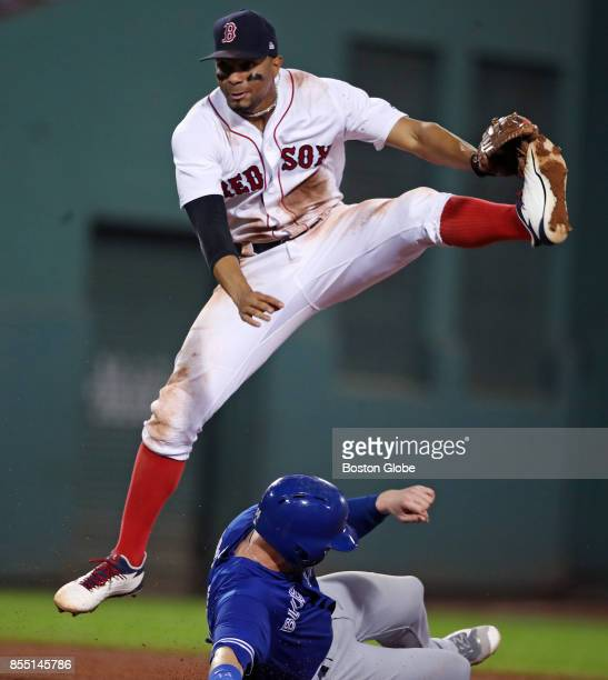 Boston Red Sox shortstop Xander Bogaerts sails over Toronto's Justin Smoak in the middle of a top of the fifth inningending double play hit into by...