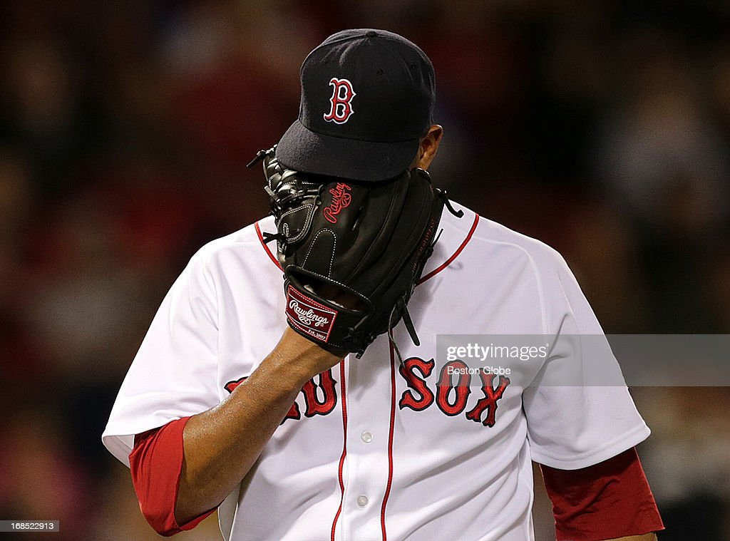 Boston Red Sox starting pitcher Felix Doubront (#22) covers his face with his glove as he heads to the dugout after the fifth inning. The Boston Red Sox take on the Minnesota Twins at Fenway Park.