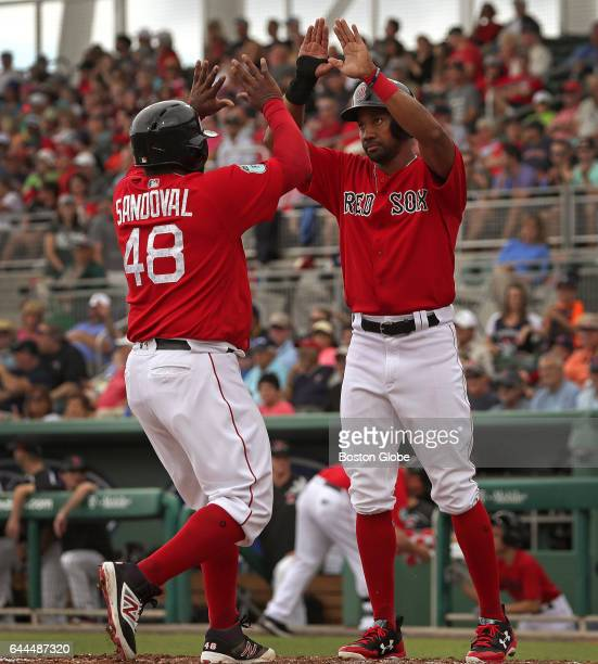 Boston Red Sox third baseman Pablo Sandoval and Boston Red Sox outfielder Chris Young high five at the plate after scoring on a three run home run by...