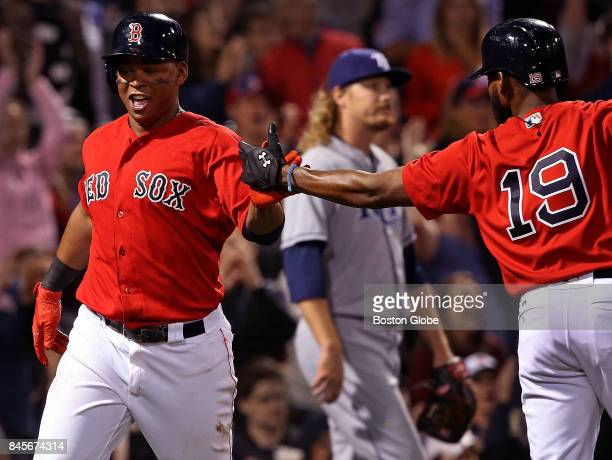 Boston Red Sox third baseman Rafael Devers is congratulated at home by Boston Red Sox center fielder Jackie Bradley Jr after scoring on an RBI double...