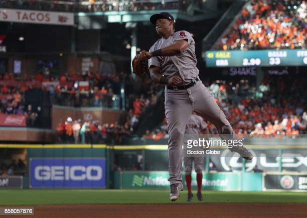 Boston Red Sox third baseman Rafael Devers leaps unsuccessfully for a line drive over his head hit by Houston Astros catcher Evan Gattis that went...